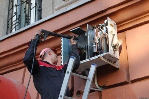 Мастер очищает наружный блок кондиционера